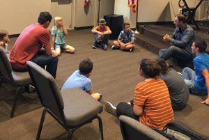 Group of young musicians sitting in a circle enjoying a lesson from the Bible about worship.